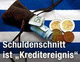 Geldbeutel mit Scheinen und Münzen auf einer griechischen Flagge