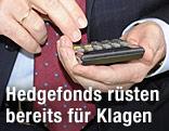Mann hält Taschenrechner in der Hand