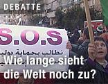 Syrische Demonstranten halten ein S.O.S.-Banner in der Hand
