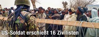 US-Soldat steht vor demonstrierenden Einwohnern in Kandahar, Afghanistan