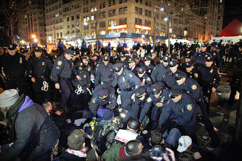 Dutzende Polizisten stehen vor mehreren sitzenden Aktivisten
