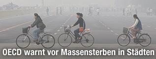 Fahrradfahrer vor einer Smog-Wolke