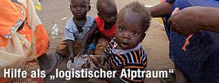 Kinder im Sudan sitzen am Boden und essen