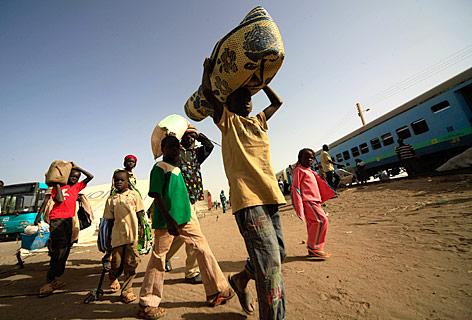 Südsudaneische Familie bei einer Bahnstation im Sudan