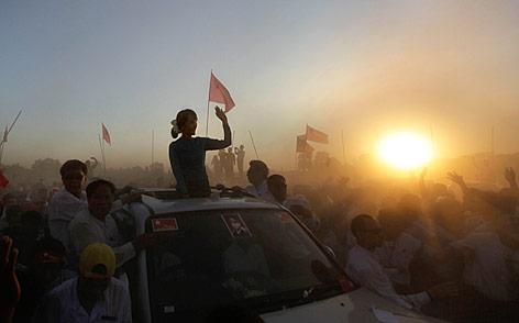 Aung San Suu Kyi wird in einem offenen Auto beim Sonnenuntergang von vielen Unterstüztern umringt