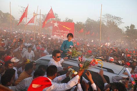 Aung San Suu Kyi wird in einem offenen Auto von vielen Unterstüztern umringt