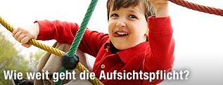 Kleinkind spielt auf einem Klettergerüst