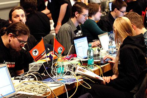 Personen sitzen an einem Tisch mit Laptops, vielen Kabeln und Wimpeln der Piratenpartei