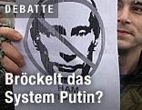 Das gezeichnete Gesicht Putins ist auf einem Plakat eines Demonstranten durchgestrichen