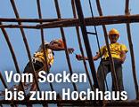 Bauarbeiter stehen auf einem Baugerüst aus Bambus