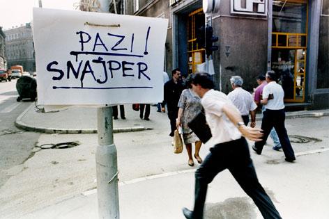 """Menschen flüchten auf der Straße, Schild mit der Aufschrift """"Vorsicht Sniper"""""""