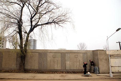 Zwei Männer stehen in Pjöngjang an einer Betonmauer und blicken nach oben