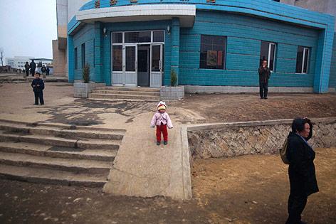 Kind vor einem blauen Haus in Pjöngjang