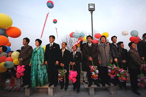 Nordkoreaner mit Luftballons und Blumen bei einer Statuenenthüllung