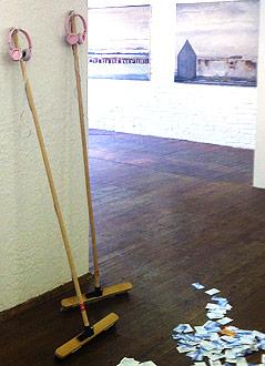 """Bild der Ausstellung """"Dust"""" zeigt Besen, Kopfhörer und Geldscheine"""
