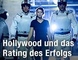 """Männer in weißen Uniformen eskortieren Schauspielerin Katniss Everdeen in """"Die Tribute von Panem"""""""
