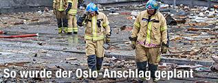 Feuerwehrleute gehen über Trümmerhaufen