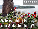 Blumen, Kerzen und eine norwegische Flagge mit der Insel Utöya im Hintergrund