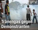 Mehrere Jugendliche laufen vor einer Tränengaspatrone weg