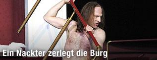 """Joachim Meyerhoff hält als """"Robinson Crusoe"""" im Burgtheater ein abmontiertes Geländer in der Hand"""
