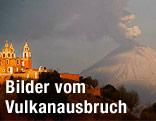 Kloster vor dem Vulkan Popocatepetl, über dem eine Rauchsäule steht