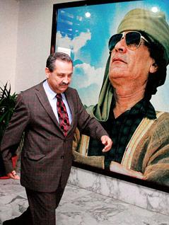 Ehemaliger libysche Ministerpräsident und Ölminister Shukri Ghanem vor einem Bild von Gaddafi
