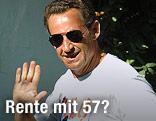 Nicolas Sarkozy in T-Shirt und mit Sonnenbrille winkt