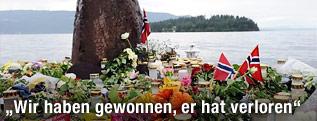 Blumen und Kerzen liegen am Festland, im Hintergrund ist die Insel Ütoya zu sehen
