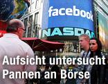 """Menschen stehen am Times Square in New York vor einer Videowand mit dem Schriftzug """"Facebook"""""""