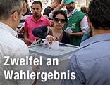 Eine syrische Frau wirft einen Stimmzettel in eine Wahlurne