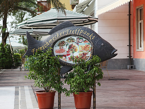 """Chinesischer Nachbau von Hallstatt, Schild in Fischform mit der Aufschrift """"Feinschmecker Treffpankt"""""""