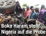 Menschen betrachten ein Autowrack nach einem Anschlag in Bauchi (Nigeria)