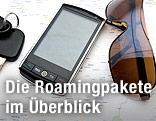 Handy neben Sonnenbrille und Autoschlüssel auf einer Landkarte