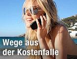 Junge Frau mit Sonnenbrille telefoniert mit Handy am Strand