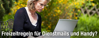 Frau sitzt im Garten und arbeitet an einem Laptop