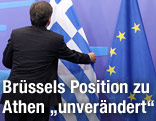 Mann zupft griechische Flagge zurecht
