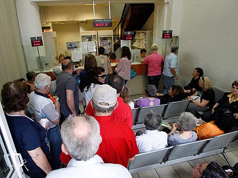 Menschen warten in einer griechischen Apotheke