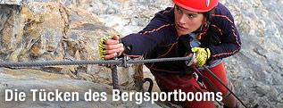 Frau hängt am Kletterseil