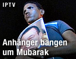 Junger Mann mit einem Bild von Hosni Mubarak