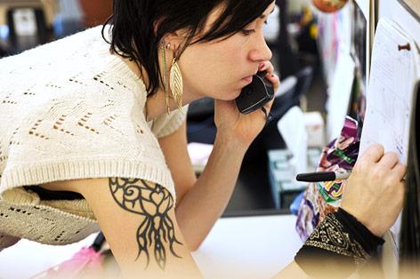 Tätowierte Frau mit einsichtigem Oberteil telefoniert