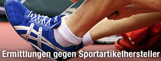 Leichtathlet bindet sich seine Asics-Laufschuhe