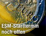 Eine Euro-Münze steht auf einer EU-Fahne