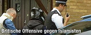 Polizist vor dem Haus eines Terrorverdächtigen