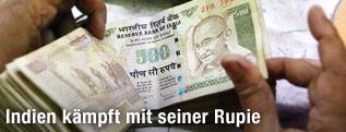 Mann zählt Rupien-Geldscheine