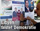 Ein Mann hängt Wahlplakate in Tripolis auf