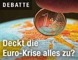 Finger drückt eine 1-Euromünze auf einen Globus