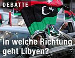 Ein Mann hält eine libysche Nationalflagge aus dem Auto