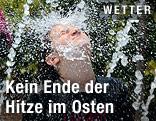 Eine Frau kühlt sich mit dem Wasser eines Springbrunnens ab