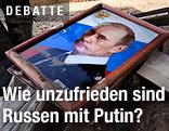 Ein Bild von Wladimir Putin liegt auf einem Müllhaufen
