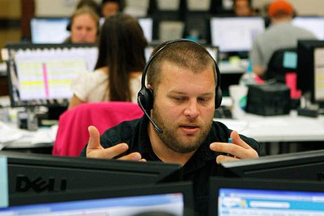 Arbeiter mit Headphone an einem Computer in einem Großraumbüro